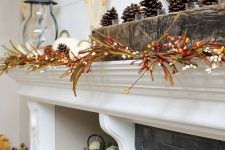 a fall mantel with berry branches, white pumpkins and wheat and some pinecones on the rough wood mantel