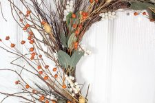 a fall twig wreath with berries, leaves, dried blooms is easy to make and it looks elegant