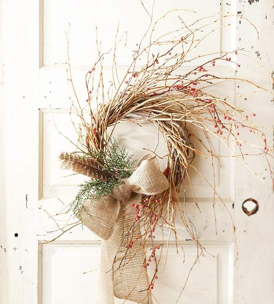 a fall twig wreath with greenery, feathers, berries and a burlap bow is a cool and easy boho decoration