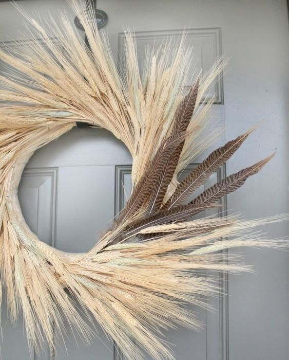 a fall wheat wreath with feathers is a bold and chic fall decoration on your front door
