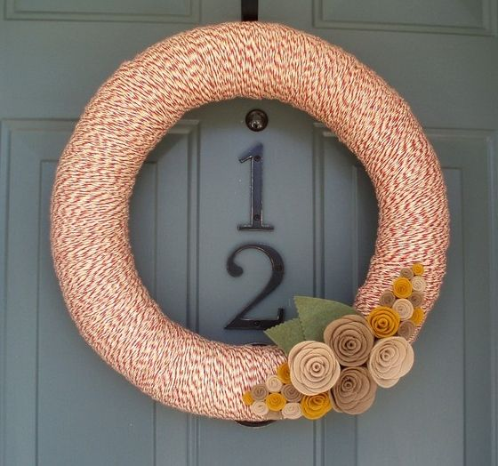 a fall wreath covered with colorful yarn with neutral fabric blooms and leaves is easy to make yourself