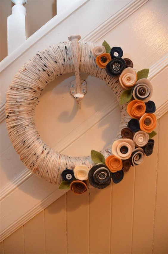 a fall wreath covered with neutral yarn, with fabric flowers with buttons is a cool idea