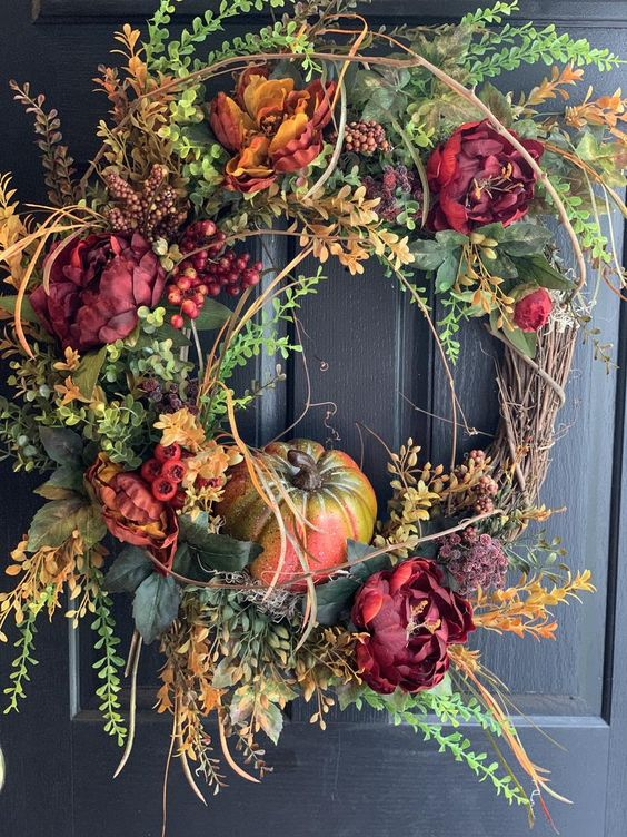 a fall wreath of leaves, faux bright blooms, pumpkins and twigs of various kinds is very chic