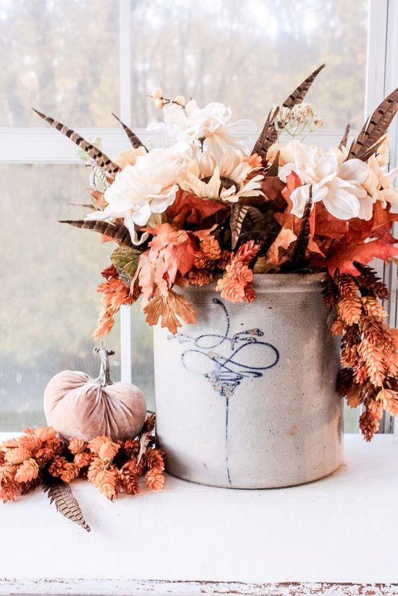 a fantastic fall boho centerpiece of white blooms, fall leaves, feathers in a bucket is a very bold and chic idea