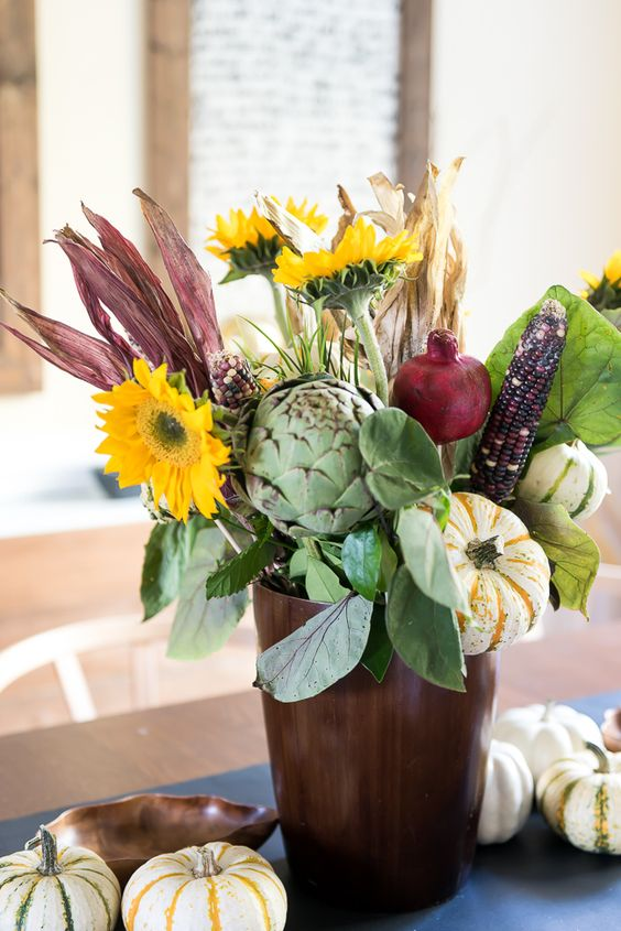 a farmhouse centerpiece of faux blooms, husks, veggies and some foliage is a cool fall decor idea