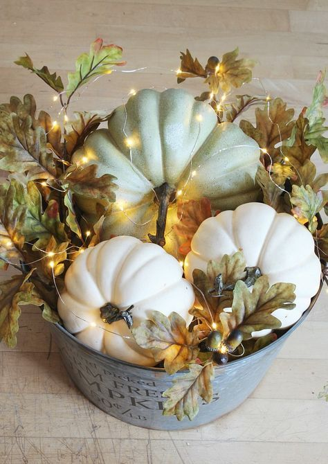 a farmhouse fall centerpiece of a bucket with fall leaves, acorns, faux pumpkins and lights is very cozy