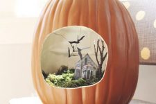 a faux pumpkin with a Halloween scene – moss, a mini house, tree and blackbirds for Halloween