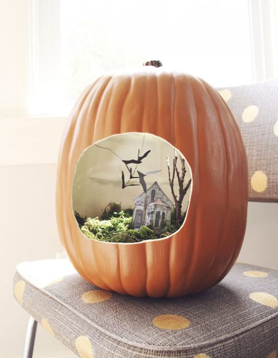 a faux pumpkin with a Halloween scene   moss, a mini house, tree and blackbirds for Halloween