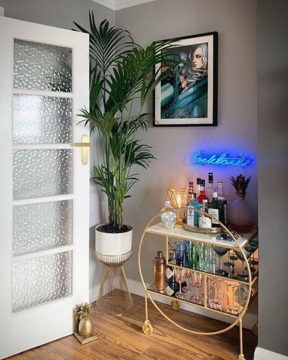 a glam home bar nook with a gold round bar with open storage spaces and a blue neon light over it