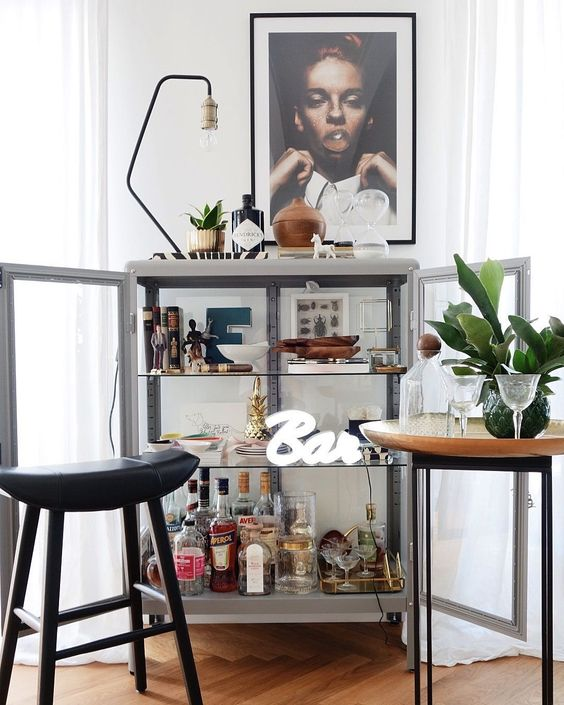 a glass bar cabinet with artworks, a lamp, some plants and a neon sign is a very chic idea