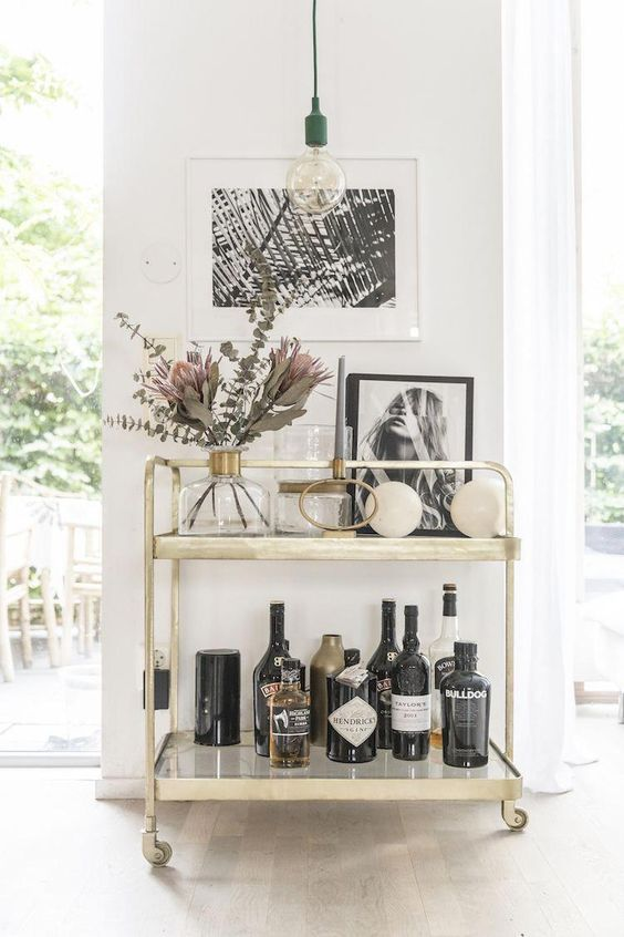 a gold bar cart with artworks, blooms and greenery is a cool idea for a modern space
