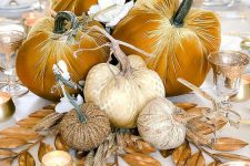 a golden fall centerpiece of mustard velvet pumpkins, dried leaves, white flowers and candles