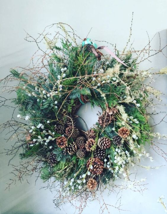 a gorgeous greenery twig fall wreath with berries, pinecones, dried grasses is very woodland-like and boho-like