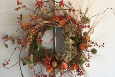 a gorgeous lush fall wreath with twigs, berries, dried blooms, leaves and wheat is lovely and bright