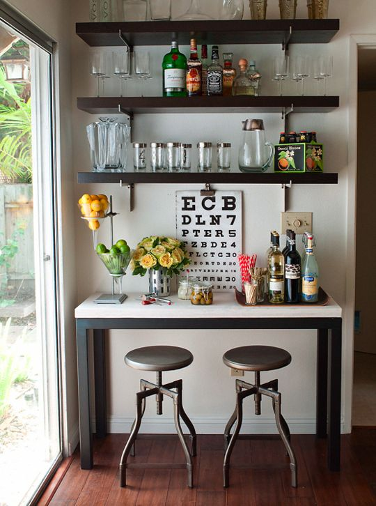 a home bar space with dark open shelves, a bar console, metal stools, blooms and an artwork make up a small yet chic nook