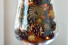 a large glass with gilded pinecones and lights is a great fall decoration or centerpiece to try