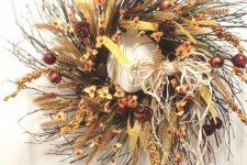 a lush twig fall wreath with faux flowers, fruits, pinecones, ribbons, feathers, wheat and hay and many other elements