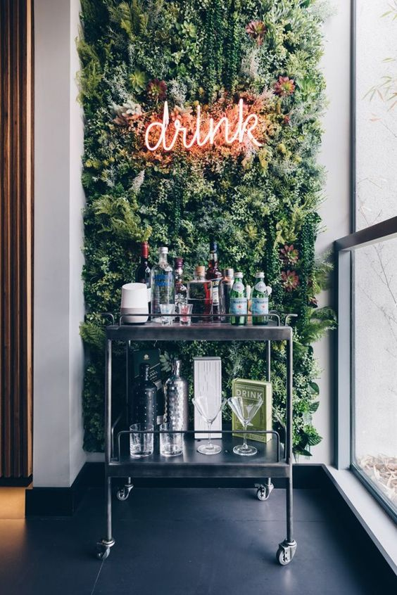 a modern home bar space with a green wall, a neon light and a metal cart with various drinks is very bold