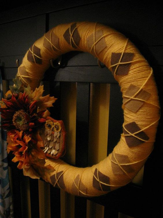 a moody fall wreath covered with orange yarn, brown fabric rhombs and faux blooms and leaves plus a play owl