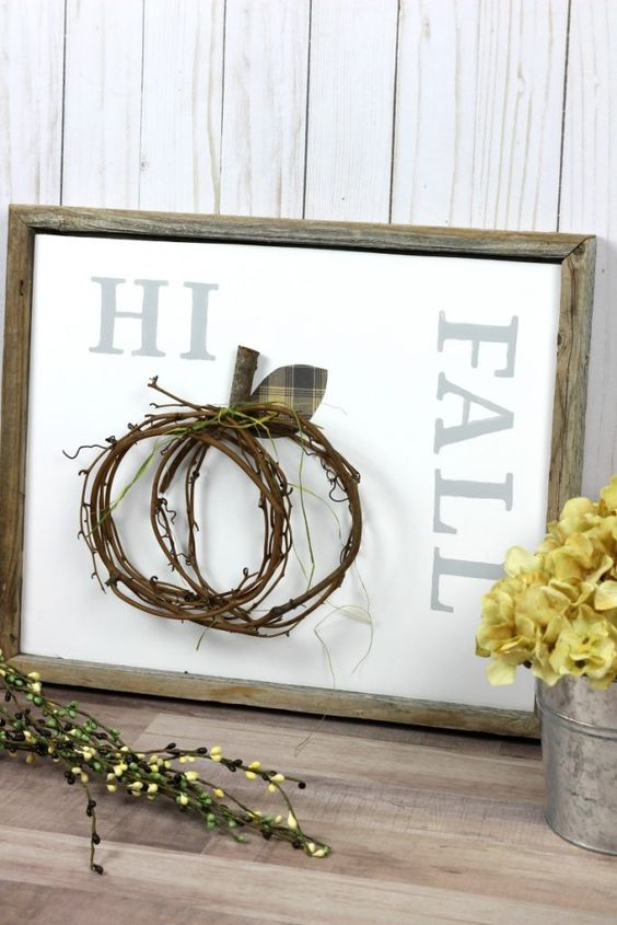 a non-typical fall sign in a reclaimed wooden frame, a twig pumpkin attached and yellow blooms next to it
