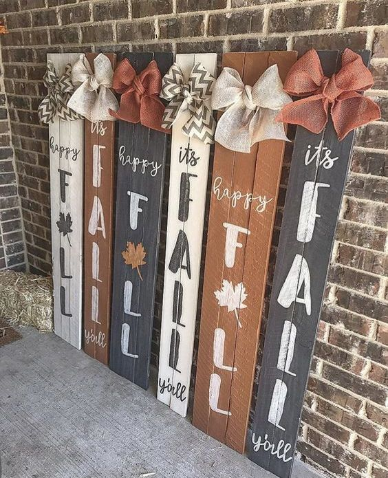 a number of fall signs in rust, black and white, all topped with contrasting burlap bows for more interest