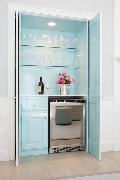 a pastel blue home bar with open glass shelves, a built-in light, a fridge and a cabinet is very romantic