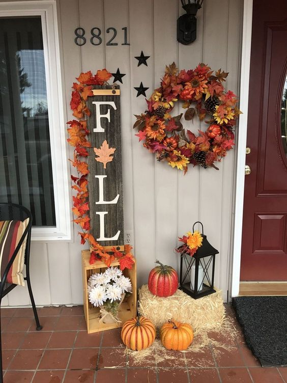 a reclaimed wood Fall sign topped with bright fake leaves, faux pumpkins, a wreath, hay and a lantern