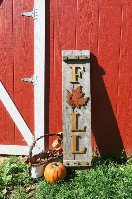 a reclaimed wood Fall sign with yellow letters and a red leaf, pumpkins and a basket with leaves