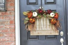 a reclaimed wood sign with fake blooms, leaves and veggies for accentign your front door in the fall