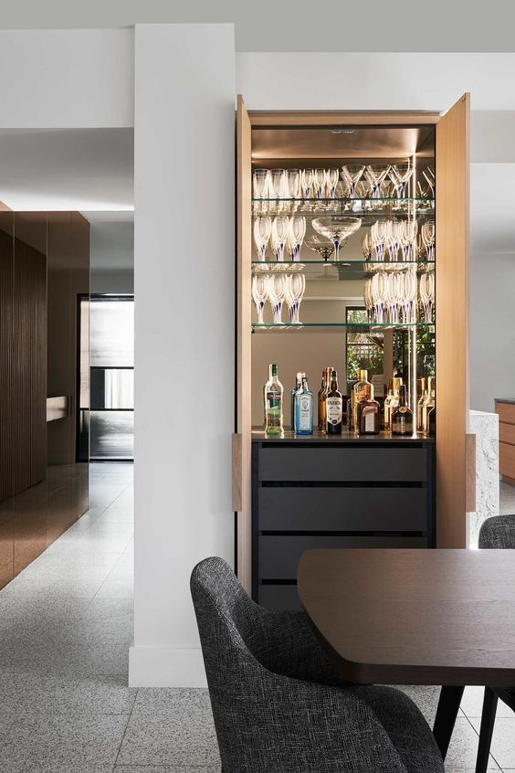 a refined built-in home bar with a mirror backsplash, glass shelves, sleek drawers and built-in lights