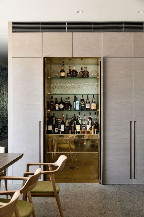 a refined built-in home bar with glass shelves and sleek gold drawers for storage is super chic