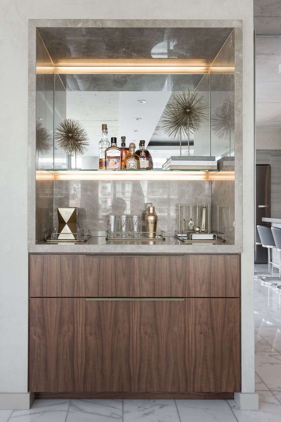 a refined built-in home bar with neutral marble, lit up shelves and sleek drawers is very chic and stylish