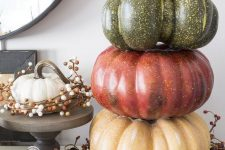 a rustic decoration – a stack of colored fall pumpkins plus a wreath of berries and acorns is a lovely idea for the fall