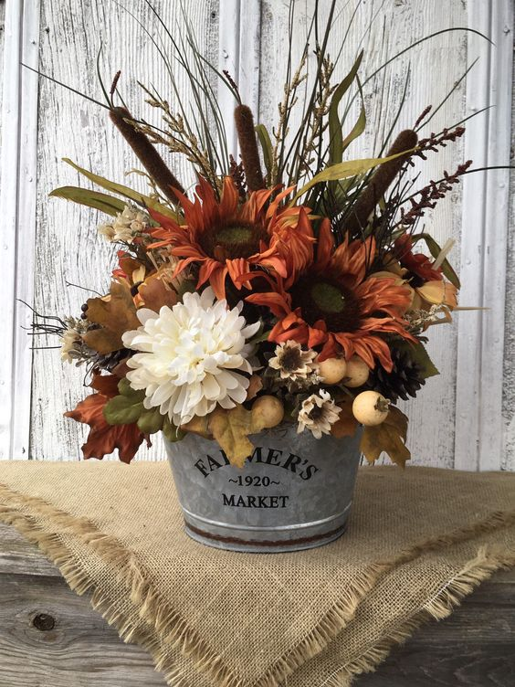 a rustic fall arrangement of rust and white faux blooms, berries, grasses, leaves and other stuff looks very cozy