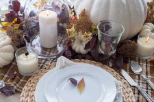 a rustic fall centerpiece of candles, white pumpkins, leaves and foliage is bright and cool