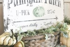 a shabby chic sign with black letters and a green pumpkin placed on a basket with greenery and surrounded by pumpkins
