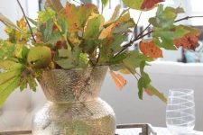 a simple and all-natural fall centerpiece of a clear vase with fall leaves put on a wooden slice