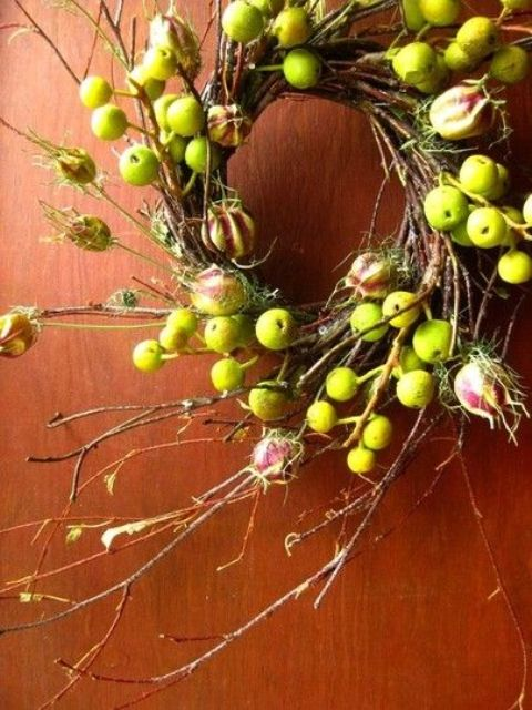 a simple and cool fall twig and branch wreath with lots of apples and blooms plus some moss