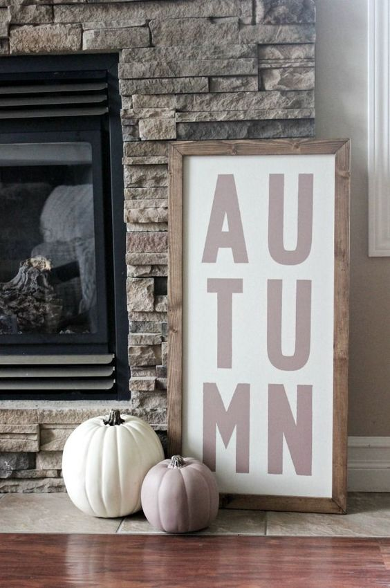 a simple contemporary sign in a stained wooden frame and a duo of pumpkins in such colors