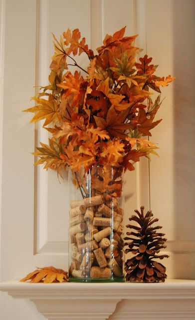 a simple fall centerpiece of a glass vase with wine corks and fall leaves on branches can be DIYed fast