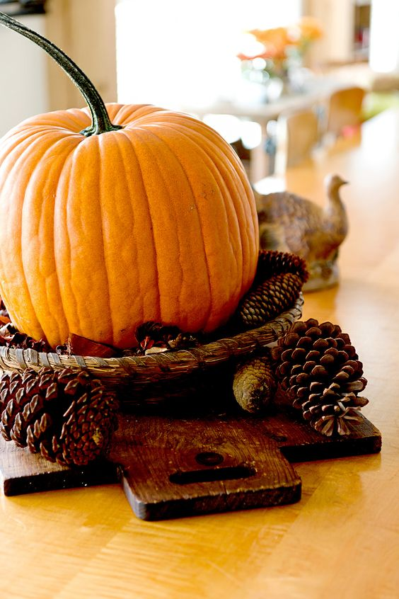 a simple fall centerpiece of a wood board, pinecones and a pumpkin in a woven tray is easy to make