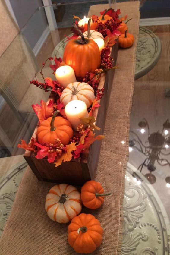 a simple fall centerpiece of a wooden box, with faux leaves, berries, pumpkins and pillar candles