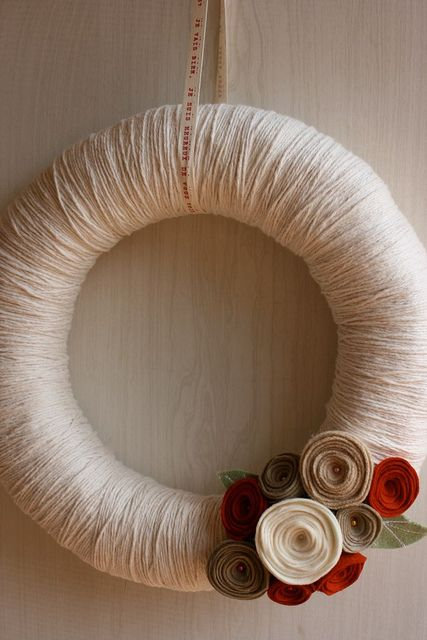 a simple fall wreath covered with neutral yarn and with bright fabric blooms and leaves is a fast DIY