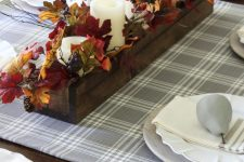 a simple rustic fall arrangement of a wooden box with pinecones, berries, fall leaves and pillar candles