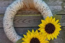 a simple summer to fall wreath covered with neutral yarn and with faux sunflowers of fabric and leaves