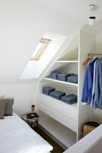 a sleek attic clothes storage item with open shelves and drawers is a stylish and comfortable idea for a small bedroom