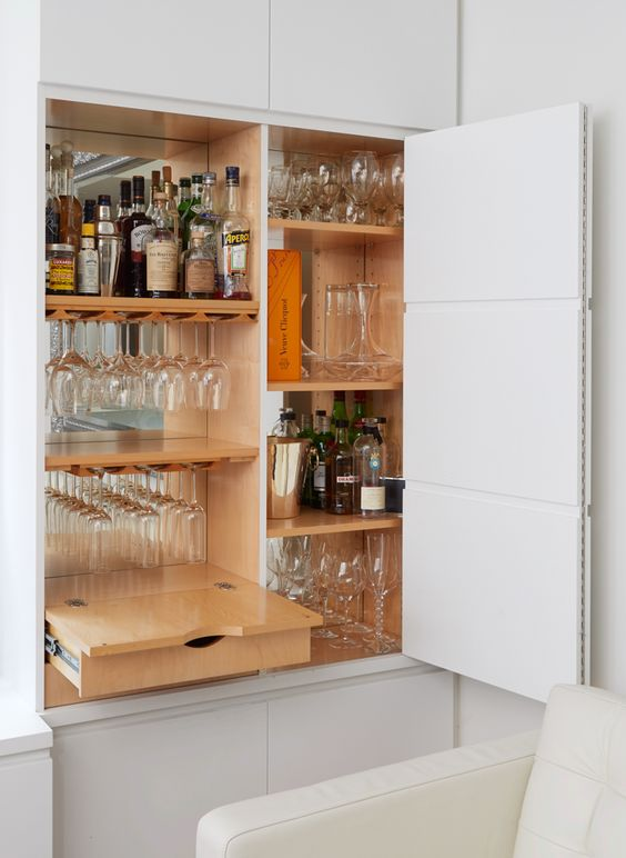 a small built-in home bar with a mirror backsplash, a drawer and shelves is a cool idea to save some space