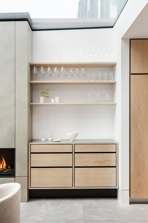 a small built-in home bar with open shelves, sleek drawers and candles is a chic addition to your living room