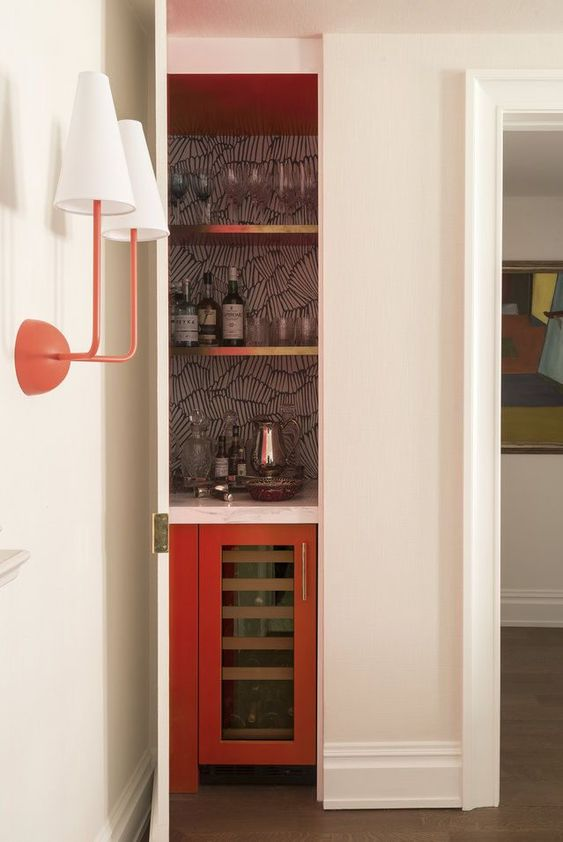 a small hidden bar with a wallpaper backsplash, open gold shelves and a fridge is chic and cool