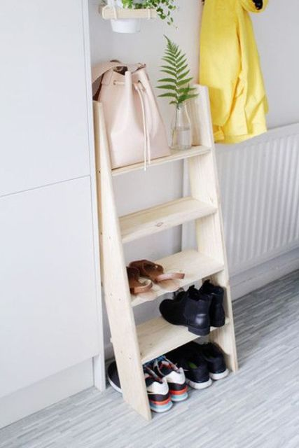 a small wooden ladder used as a shelf for shoes and bags is a simple idea for a bedroom or entryway